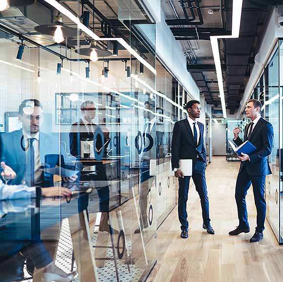 iMeta Technologies Multiethnic partners having conversation in office corridor